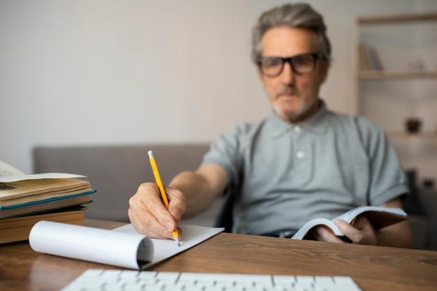 Senior man die aantekeningen maakt in de klas