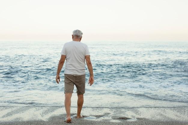 Senior man die alleen op het strand loopt
