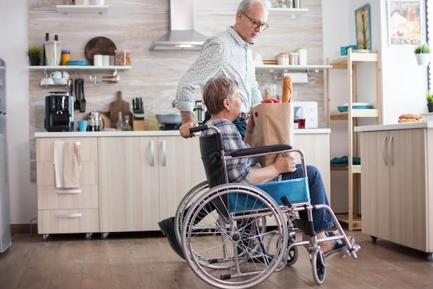 Senior man die boodschappentas neemt van gehandicapte vrouw in rolstoel. volwassen mensen met verse groenten van de markt. leven met een gehandicapte met een loophandicap