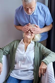 Senior man die de ogen van de vrouw bedekt en verrassing maakt, grijsharige man in vrijetijdskleding gaat zijn vrouw thuis plezieren. vrouw zit op de bank