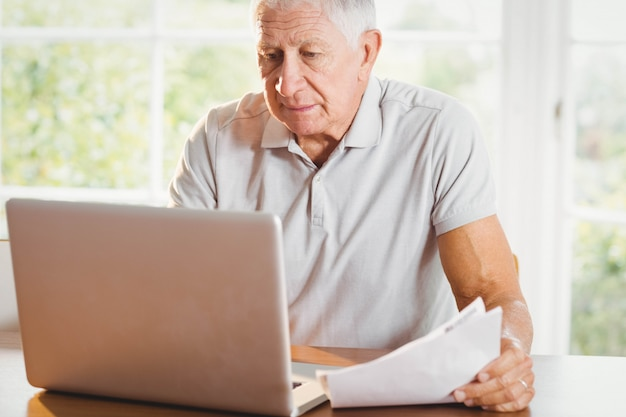 Senior man die documenten en thuis laptop gebruikt