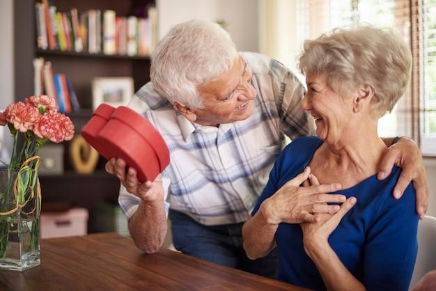 Senior man die een cadeau geeft aan zijn vrouw