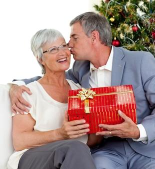 Senior man die een kus en een kerstcadeau geeft aan zijn vrouw