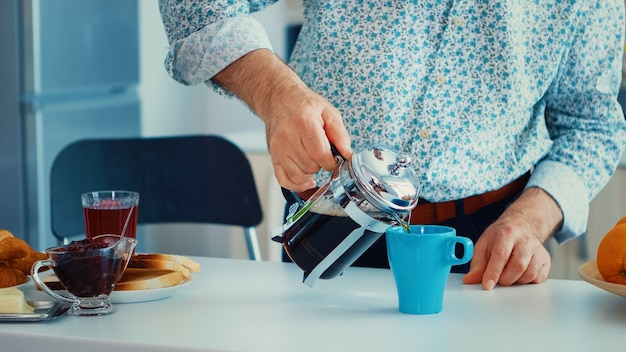 Senior man die franse pers gebruikt voor koffiebereiding en het in een mok giet. bejaarde in de ochtend genietend van vers bruin café espressokopje cafeïne uit vintage mok, filter ontspannen verfrissing