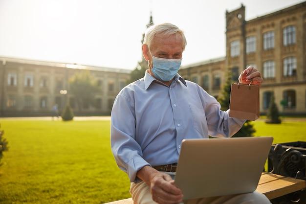 Senior man die gezondheidsresultaten online controleert met laptop