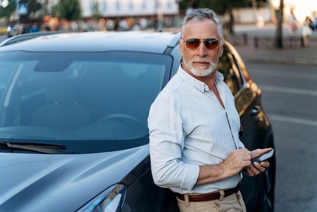 Senior man die in de buurt van zijn suv-auto staat en smartphone vasthoudt. portret van een man van middelbare leeftijd buiten in de buurt van zijn auto