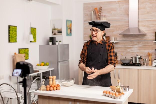 Senior man die inhoud maakt voor culinaire blog en het recept stap voor stap uitlegt