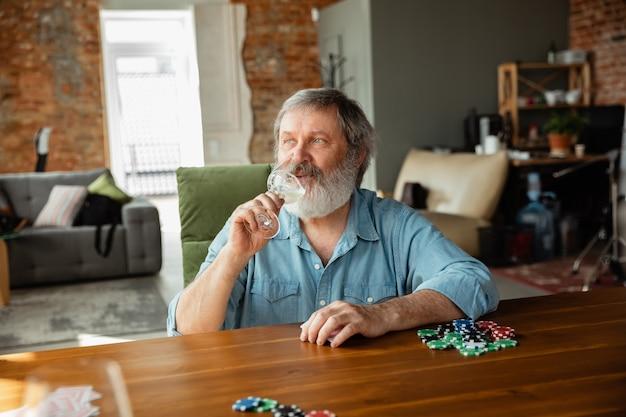Senior man die kaarten speelt en wijn drinkt met vrienden ziet er gelukkig uit