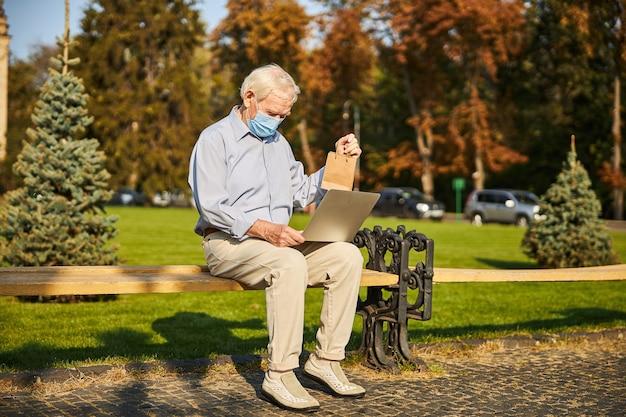 Senior man die laptop gebruikt terwijl hij naar het scherm kijkt