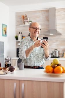 Senior man die online winkelt met smartphone en creditcard vasthoudt tijdens het ontbijt in de keuken. gepensioneerde bejaarde die internetbankieren gebruikt om thuis te betalen met moderne technologie