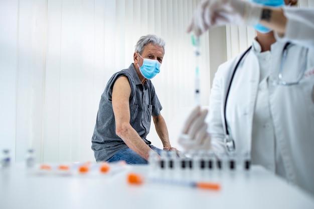 Senior man die op het punt staat vaccin te krijgen in de kliniek tijdens coronaviruspandemie om gezond te blijven