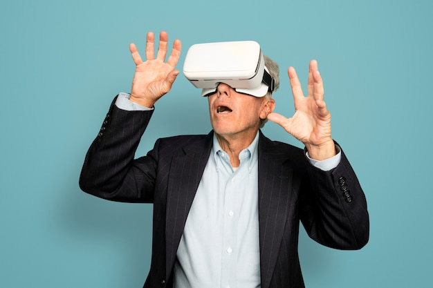 Senior man die plezier heeft met het digitale apparaat van de vr-headset