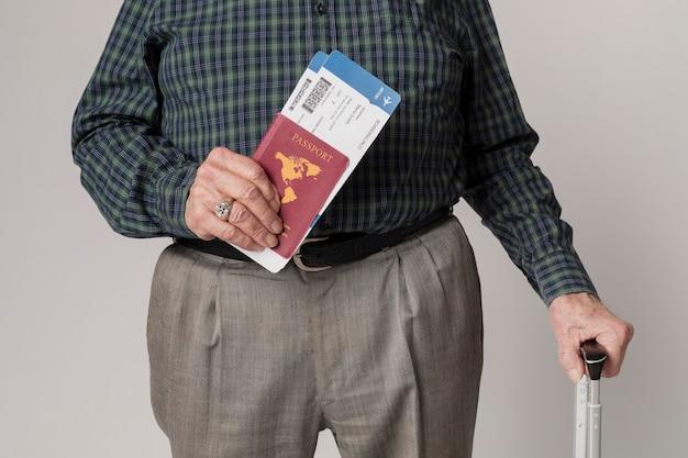 Senior man die reist met zijn paspoort en bagage