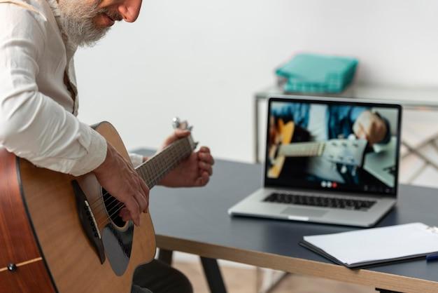 Senior man die thuis gitaarlessen studeert op laptop