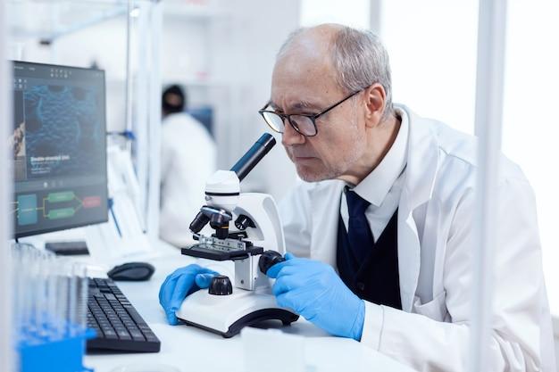 Senior man die wetenschappelijk onderzoek uitvoert en door een microscoop kijkt. chemicus-onderzoeker in steriel laboratorium die experimenten doet voor de medische industrie met behulp van moderne technologie.