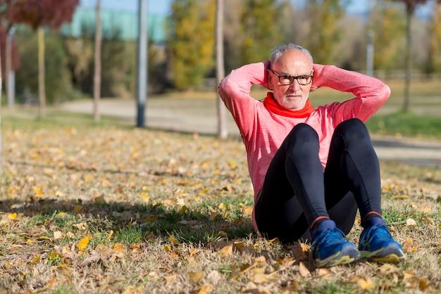Senior man die zich uitstrekt na het joggen in het park