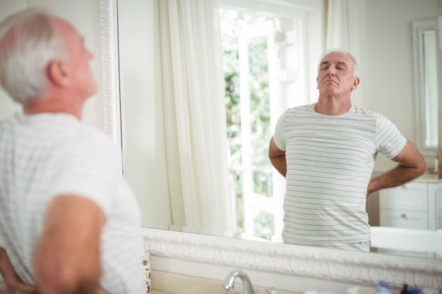 Senior man die zich uitstrekt voor de spiegel