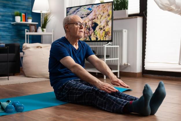 Senior man die zijn benen uitrekt terwijl hij op yogamat in de woonkamer zit tijdens pilatestraining