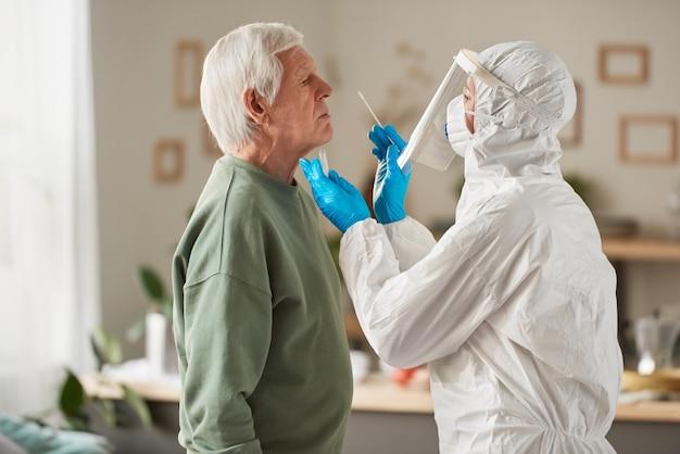 Senior man die zijn mond opent terwijl arts in beschermende kleding een monster neemt voor coronavirustest