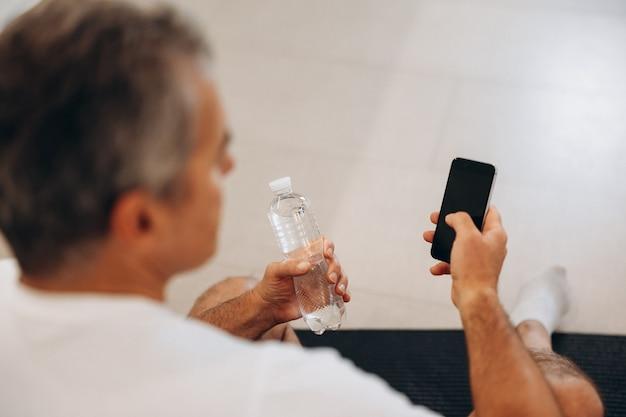 Senior man die zijn smartphone gebruikt en een plastic waterfles vasthoudt