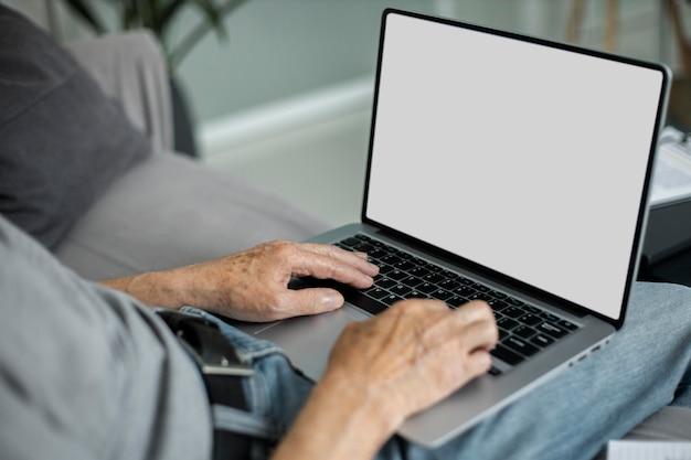 Senior man doet online lessen op een laptop