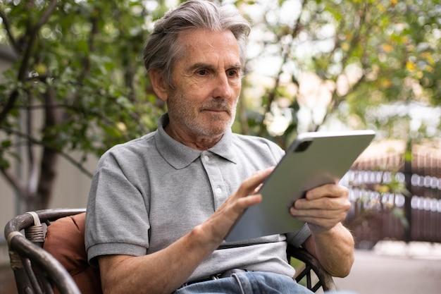 Senior man doet online lessen op een tablet