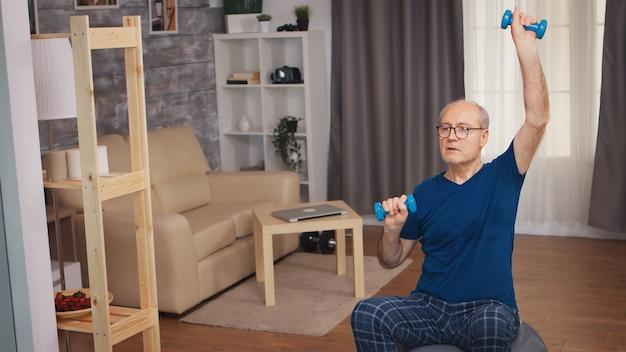 Senior man doet schouderpers met halters in de woonkamer. bejaarde gepensioneerde gezonde opleiding gezondheidszorg sport thuis, fitness activiteit uitoefenen op oudere leeftijd