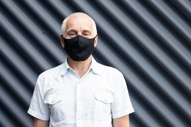 Senior man draagt beschermend masker tegen infectieziekten en griep