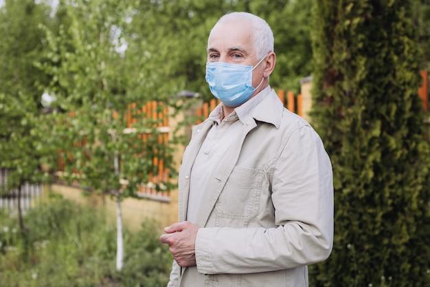 Senior man draagt een beschermend masker. de natuur als redding van het virus. senior man met masker op gezicht.
