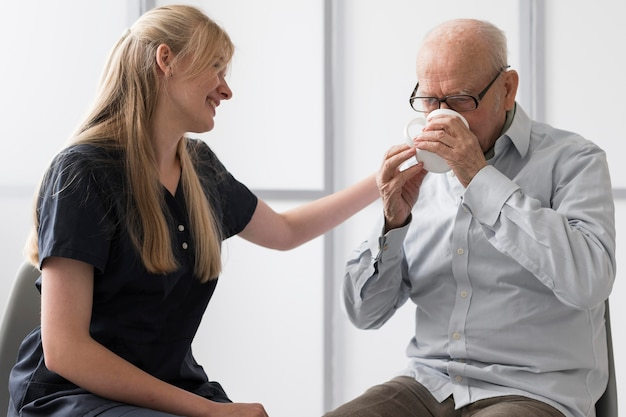 Senior man drinkwater met verpleegster hem troosten
