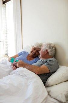 Senior man een verrassingsgeschenk geven aan vrouw in de slaapkamer thuis