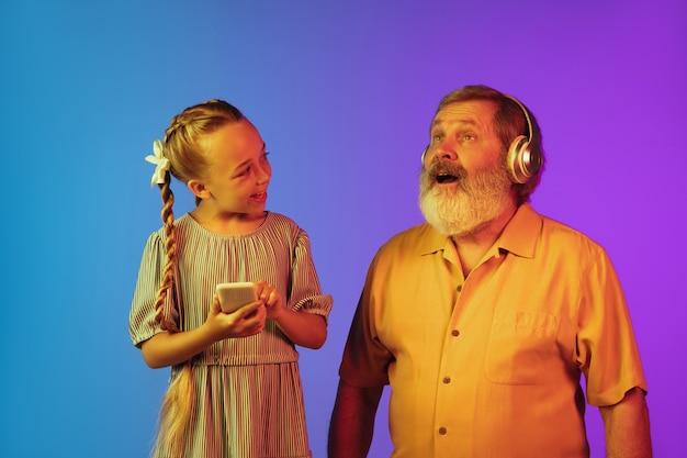 Senior man en kleindochter op neon oppervlak