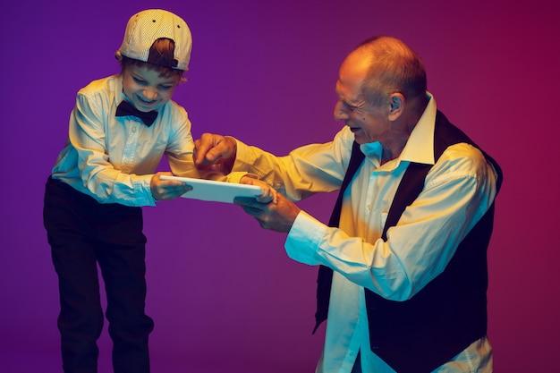 Senior man en kleine jongen op gradiëntachtergrond, copyspace