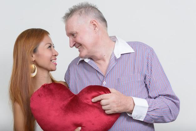 Senior man en volwassen aziatische vrouw als paar samen en verliefd tegen wit