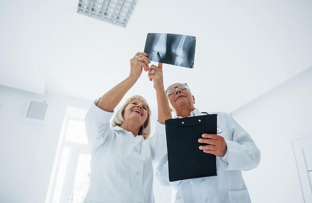 Senior man en vrouw artsen in wit uniform onderzoekt röntgenfoto's van menselijke benen.