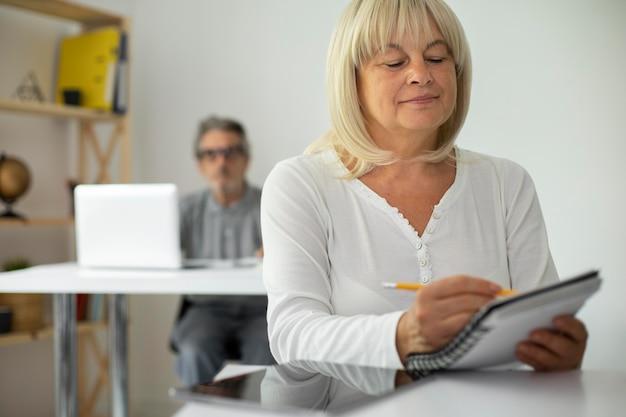 Senior man en vrouw die opletten in de klas