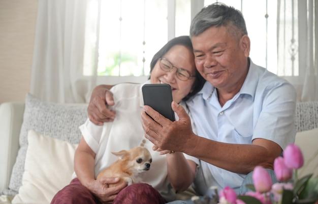 Senior man en vrouw gebruiken smartphone voor videogesprekken in huis met chihuahua hond.