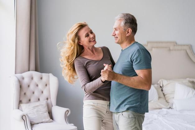 Senior man en vrouw hand in hand en glimlachen