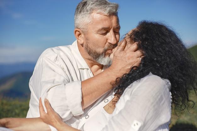 Senior man en vrouw in de bergen. volwassen paar verliefd bij zonsondergang. man in een wit overhemd. mensen zitten op een hemelachtergrond.