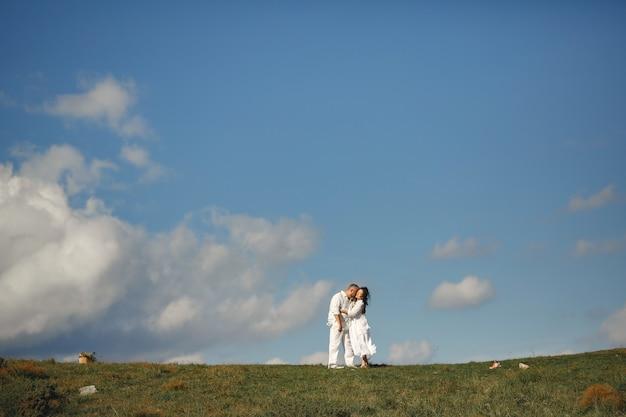 Senior man en vrouw in de bergen. volwassen paar verliefd bij zonsondergang. man in een wit overhemd.