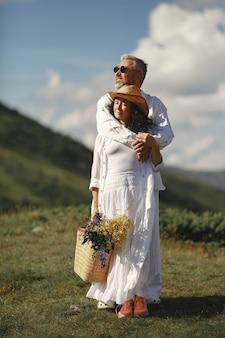 Senior man en vrouw in de bergen. vrouw met mand met bloemen. man in een wit overhemd.