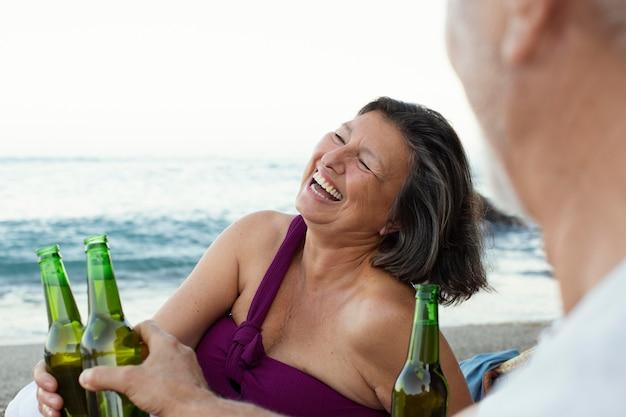 Senior man en vrouw lachen op het strand terwijl ze bier drinken