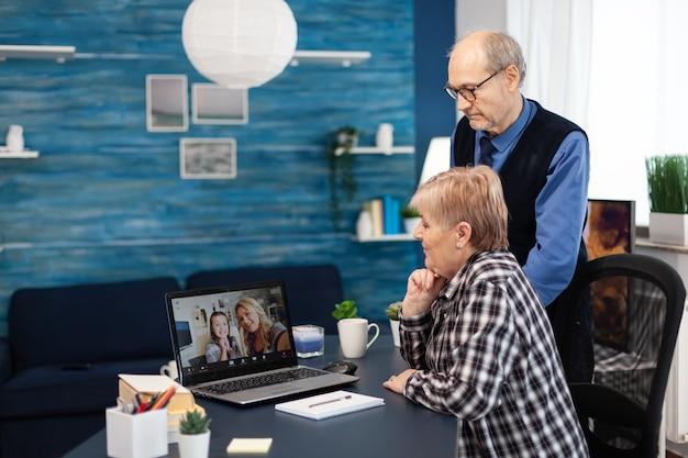 Senior man en vrouw praten met nichtje tijdens videogesprek