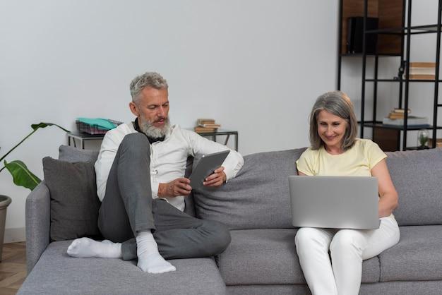 Senior man en vrouw thuis op de bank met laptop en tablet