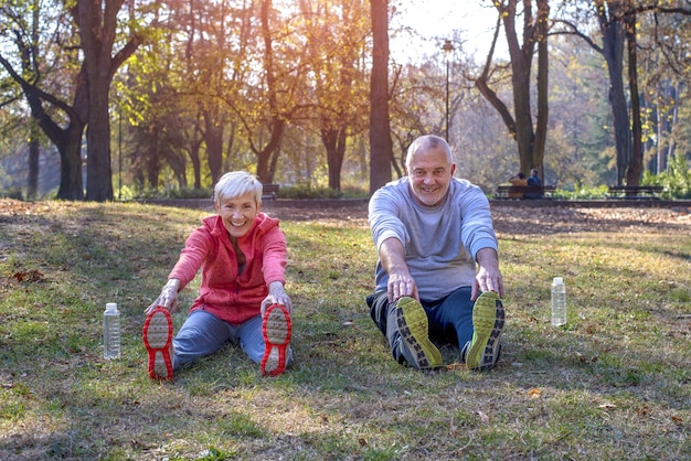 Senior man en vrouw trainen in het park in de herfst