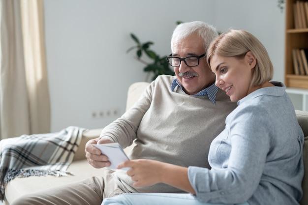 Senior man en zijn jonge dochter kijken naar een van hun familiefoto's terwijl ze op hun gemak op de bank ontspannen en foto's bespreken