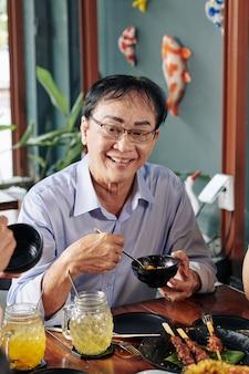 Senior man eten met stokjes