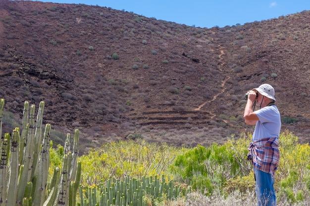 Senior man geniet van vrijheid en excursie in de buitenlucht in de bergen, wegkijkend met een verrekijker