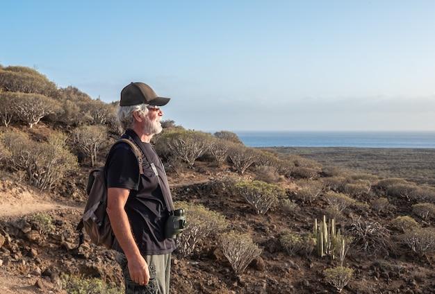 Senior man genieten van wandelen in dorre vulkanische landschap. kijkend naar de horizon over zee. rugzak en verrekijker, jeugdige ouderen gezonde levensstijl