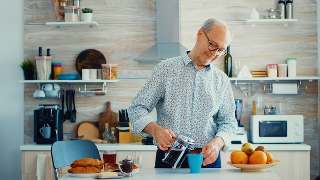 Senior man gieten warme koffie uit de franse pers in de keuken tijdens het ontbijt. bejaarde in de ochtend genietend van vers bruin café espressokopje cafeïne uit vintage mok, filter ontspannen verfrissing